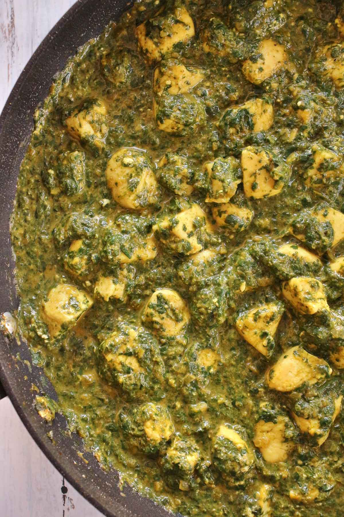 Closeup of chicken saag curry in a wide skillet.