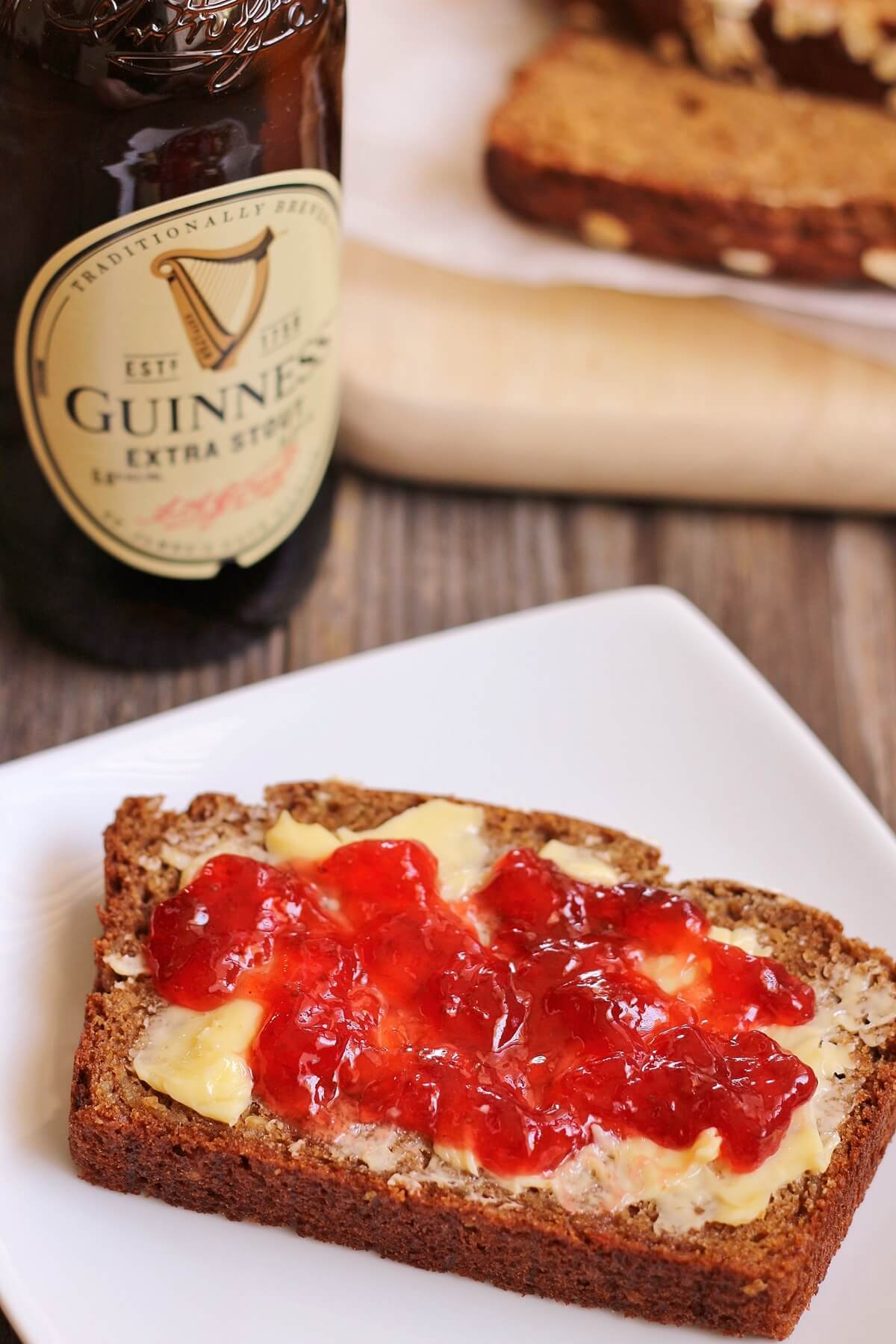 closeup of a slice of Irish Guinness brown bread with butter and jam