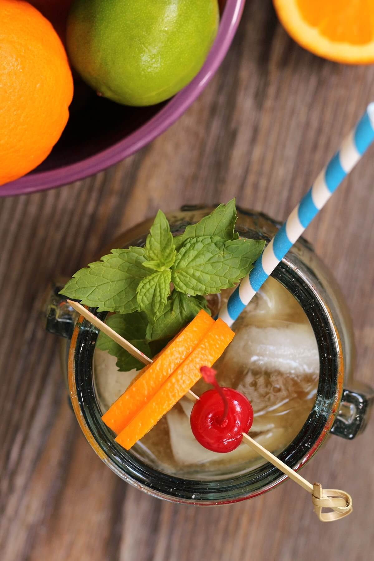 overhead view of a tiki drink garnished with mint, orange, and maraschino cherry