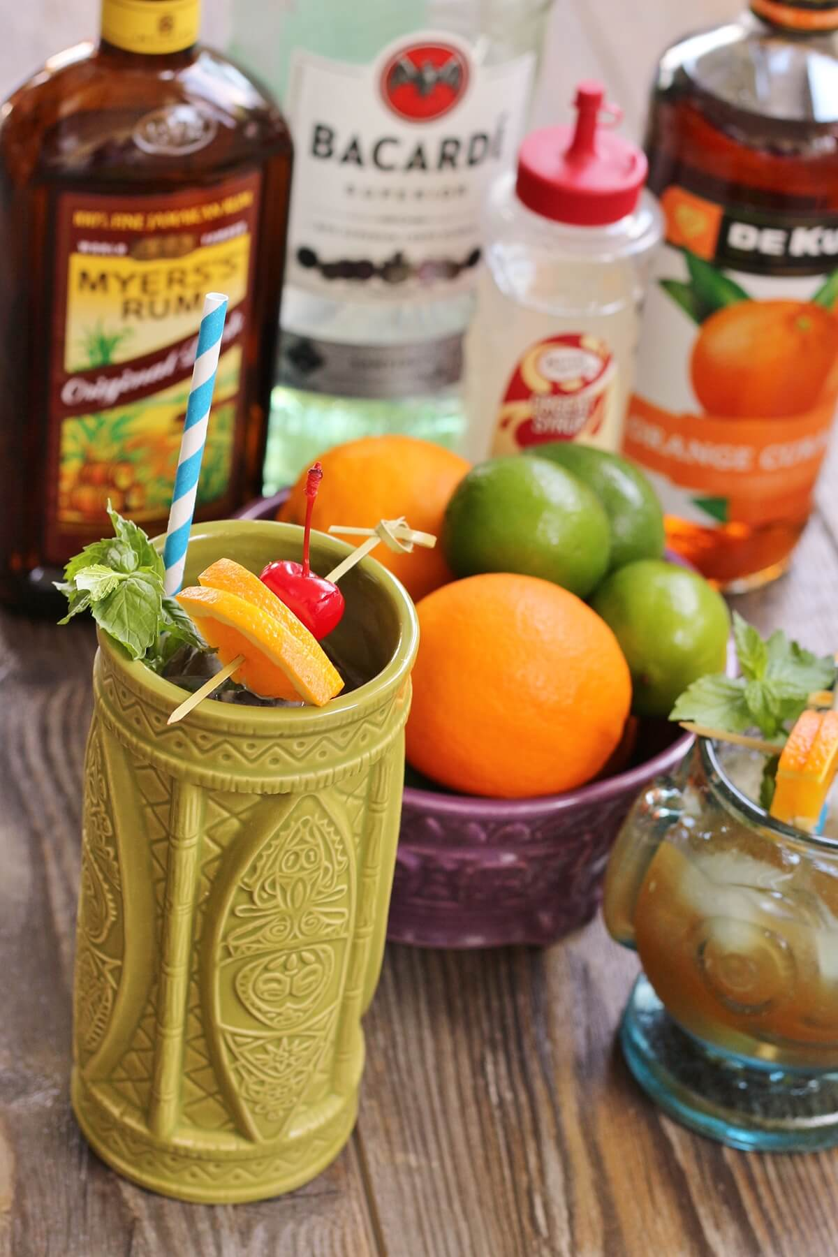 two tiki drinks, a bowl of oranges and limes, and bottles of liquor