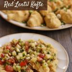 a closeup of a plate of red lentil kofte topped with colorful chopped salad