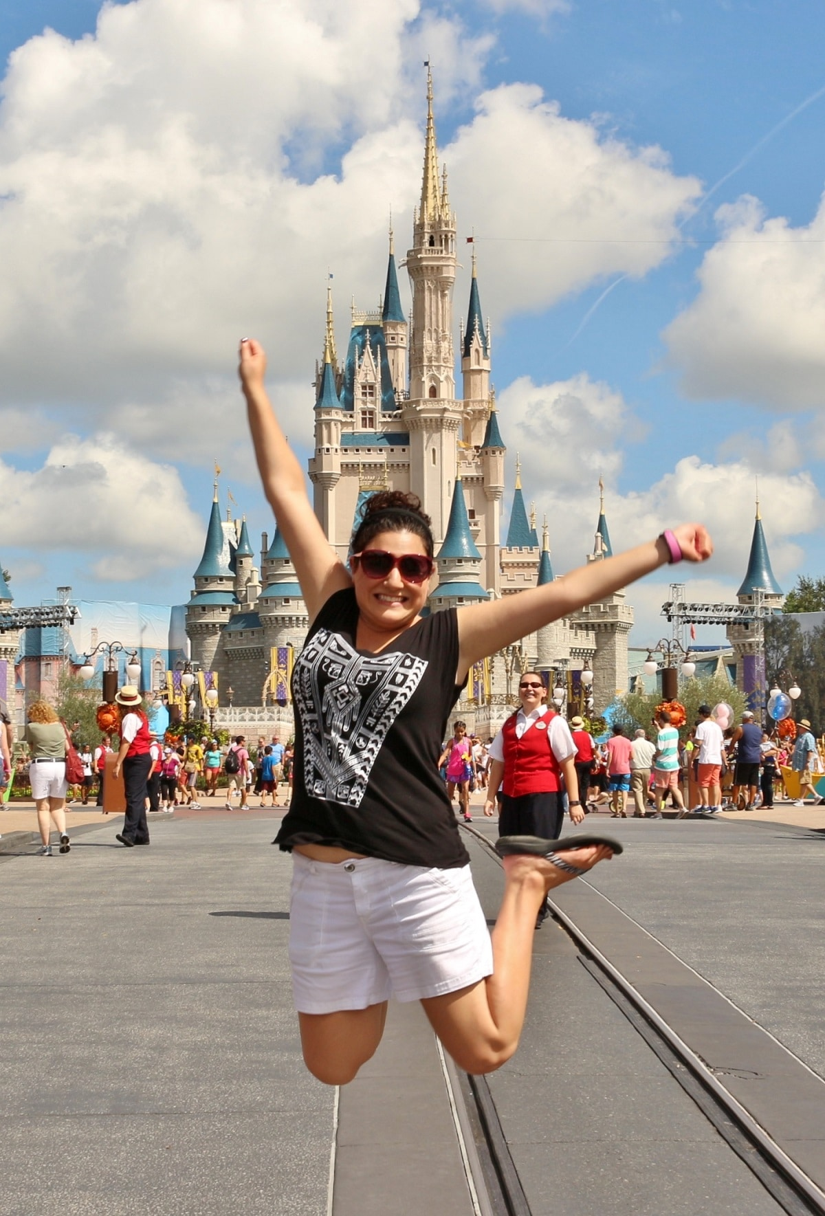 a woman jumping in front of Cinderella Castle in Disney's Magic Kingdom