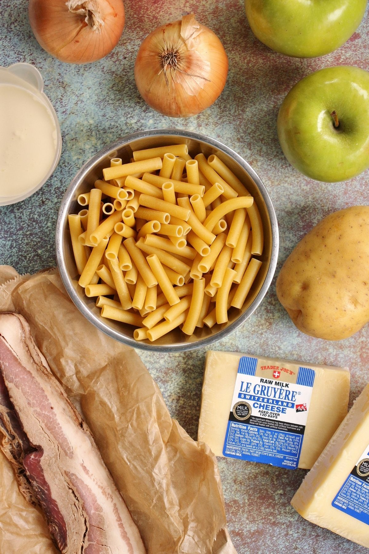 overhead view of ingredients for Alpine macaroni including ziti, cheese, potato, onions, apples, and bacon