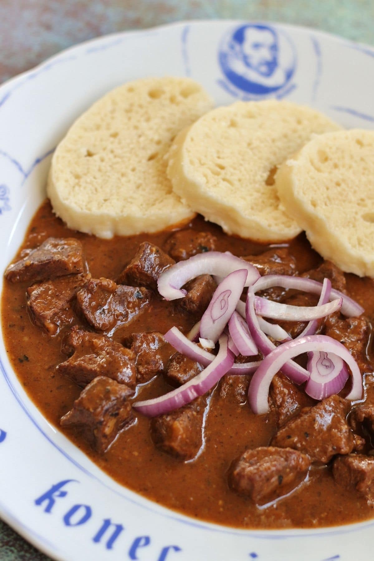 Czech goulash with sliced red onion and dumplings on a white plate