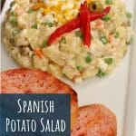 Spanish potato salad on a white plate with tomato-rubbed bread