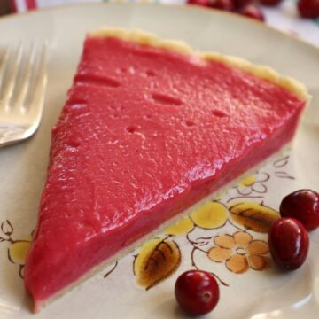 Closeup of a slice of cranberry curd tart on a plate with 3 cranberries.
