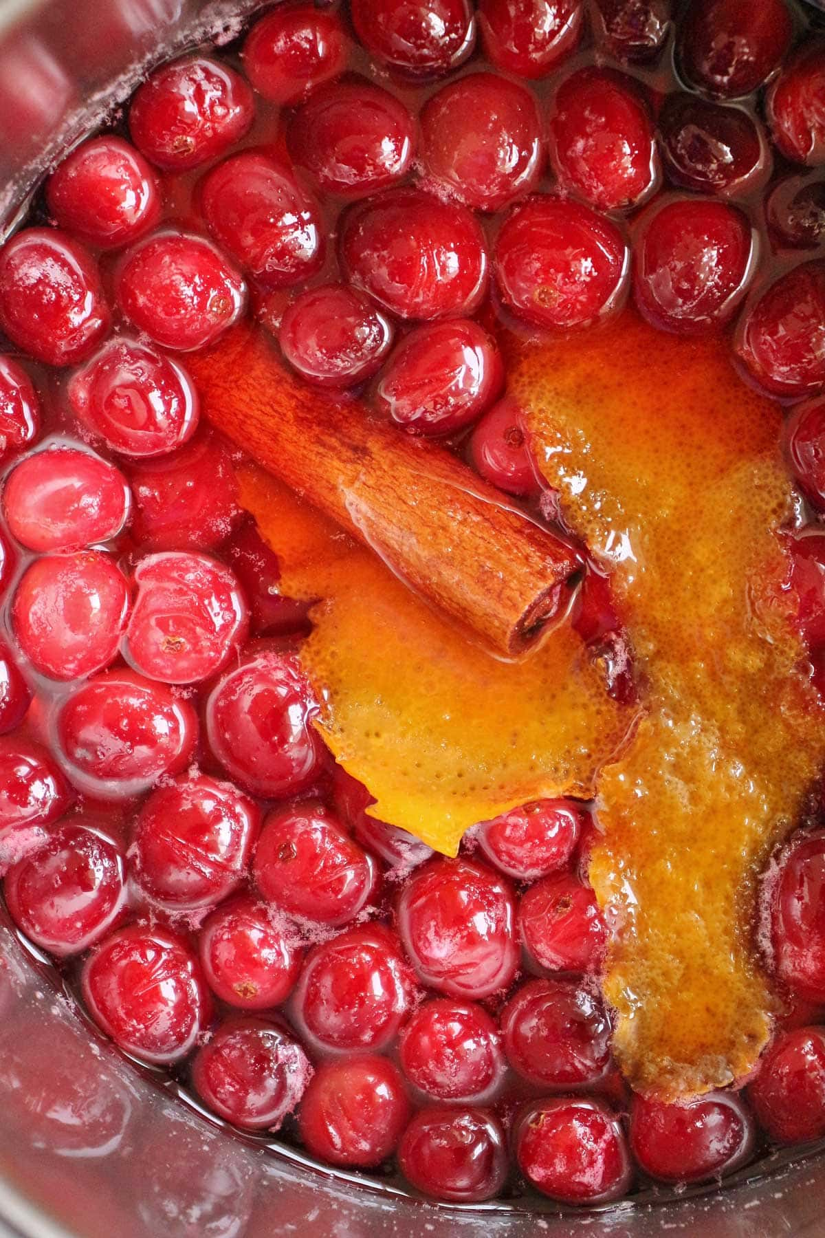 Closeup of fresh cranberries in syrup with a cinnamon stick and orange zest strips.