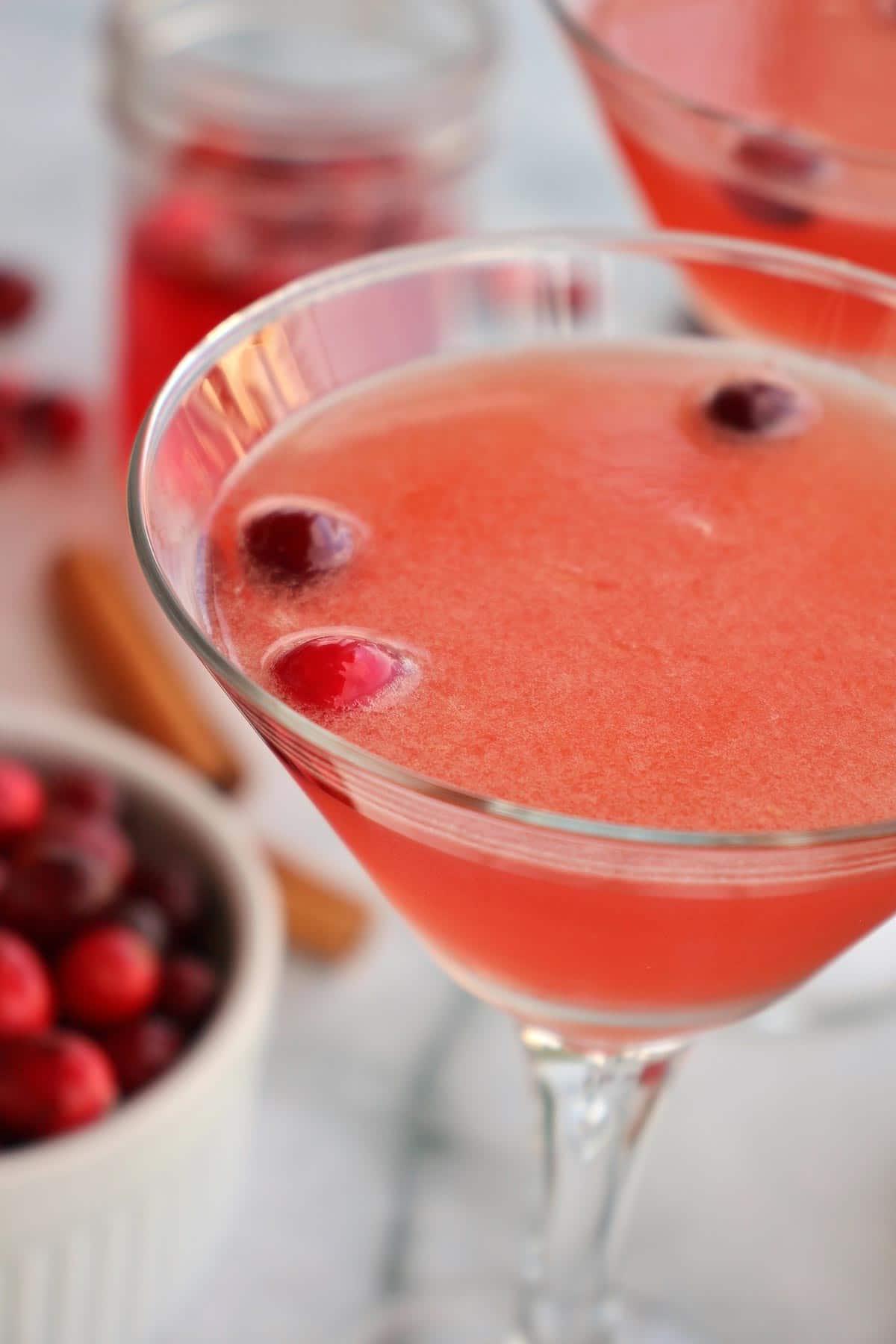 Closeup of a cranberry daiquiri cocktail in a martini glass.