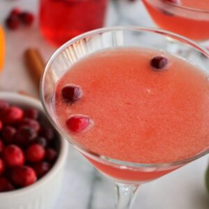 Closeup of a pink cranberry cocktail in a martini glass with 3 cranberries floating in it.