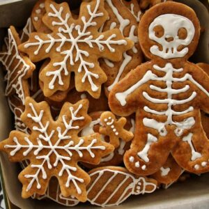 Closeup of a cookie tin filled with gingerbread cookies shaped like snowflakes and skeletons.