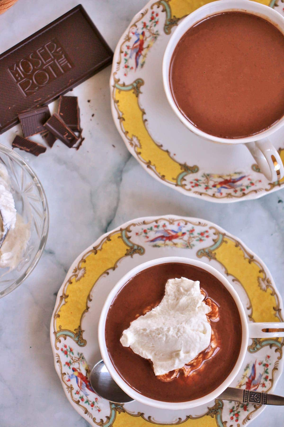 Two tea cups filled with hot chocolate, one topped with whipped cream.