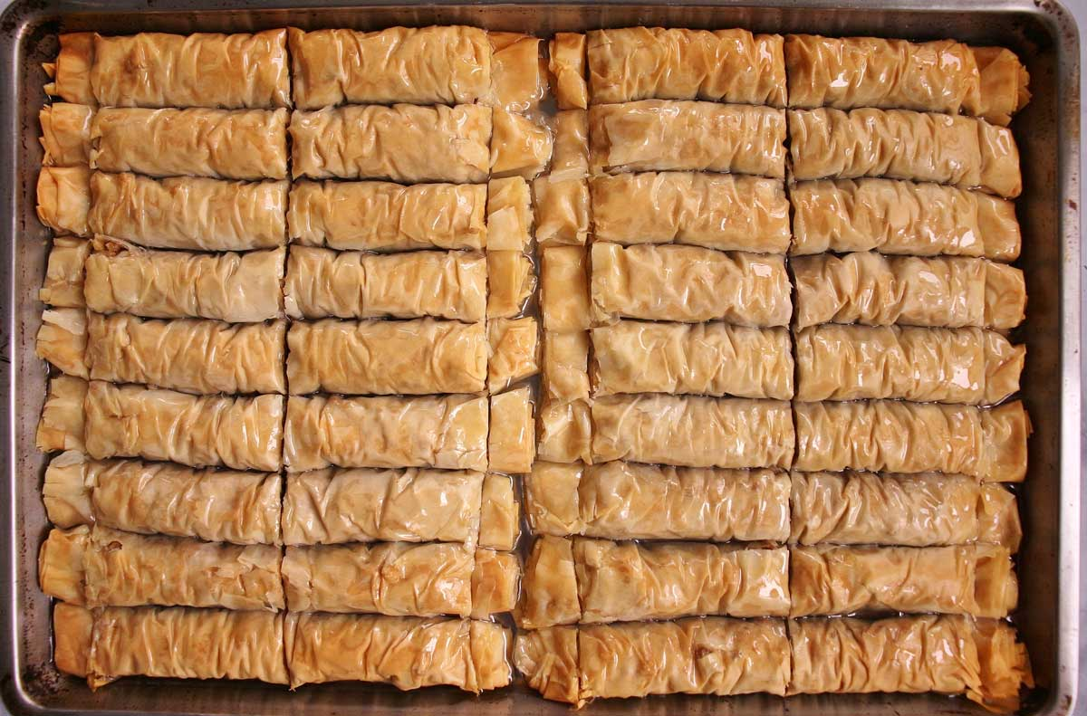 A sheet pan of baked rolled baklava after pouring the syrup over it.