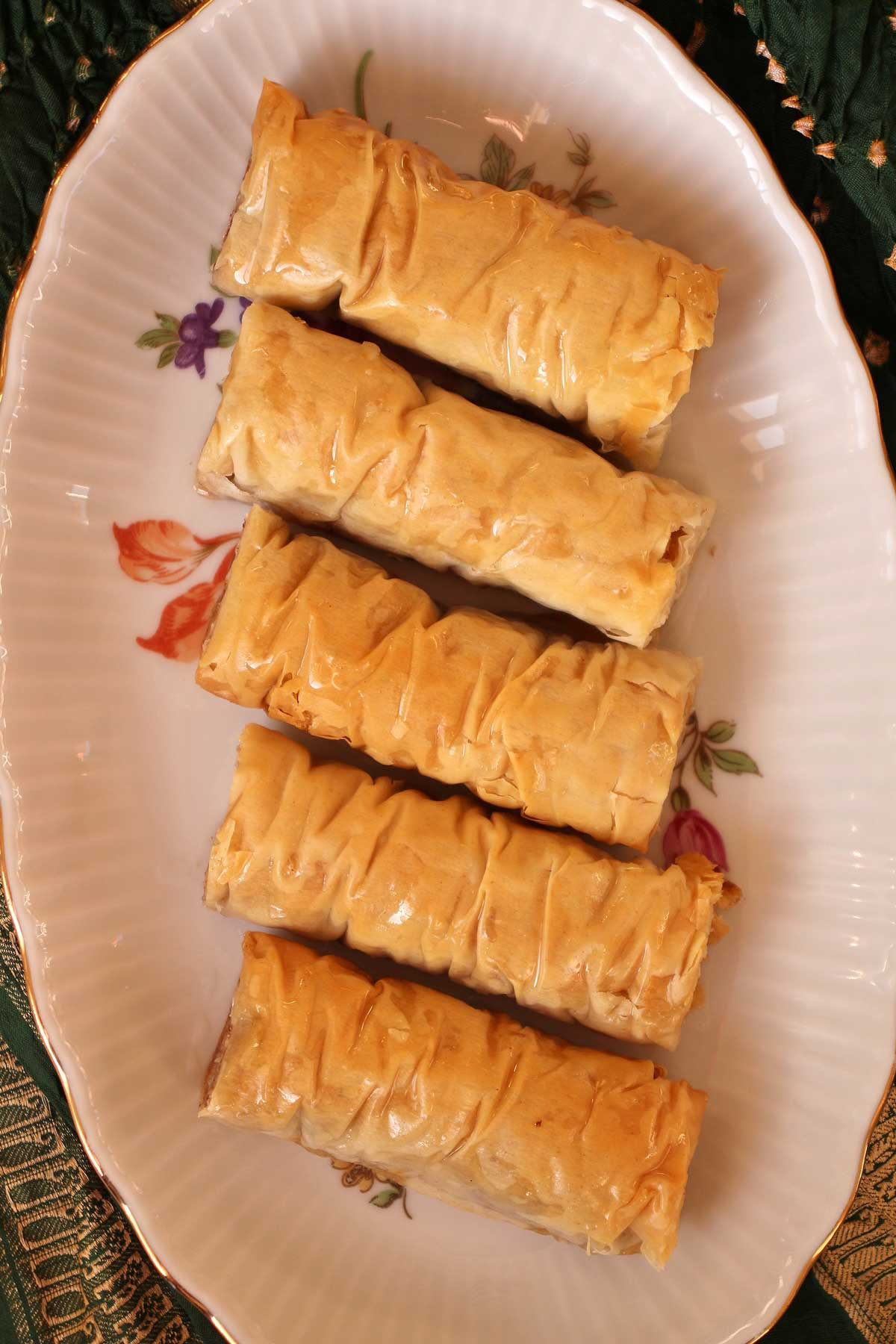 Five rolled baklavas lined up on an oval serving dish.