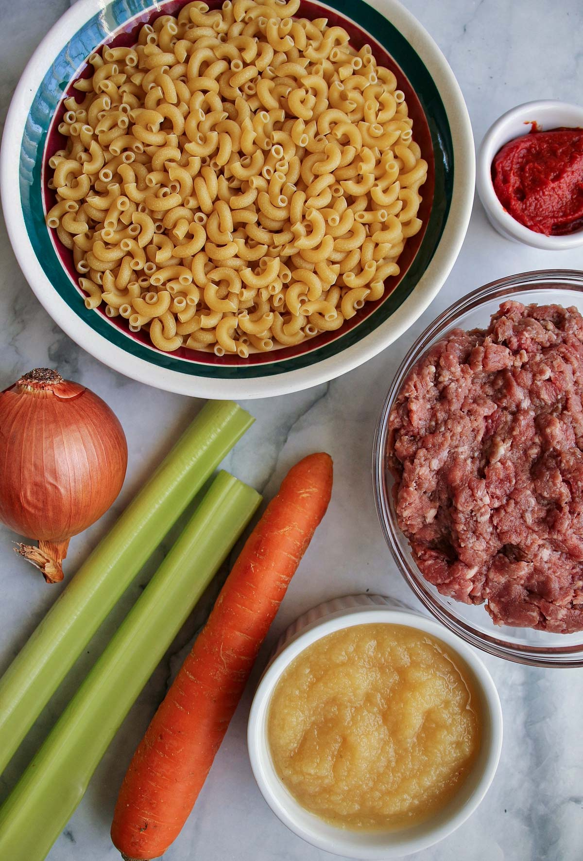 Elbow macaroni, an onion, celery, carrot, applesauce, ground beef, and tomato paste.