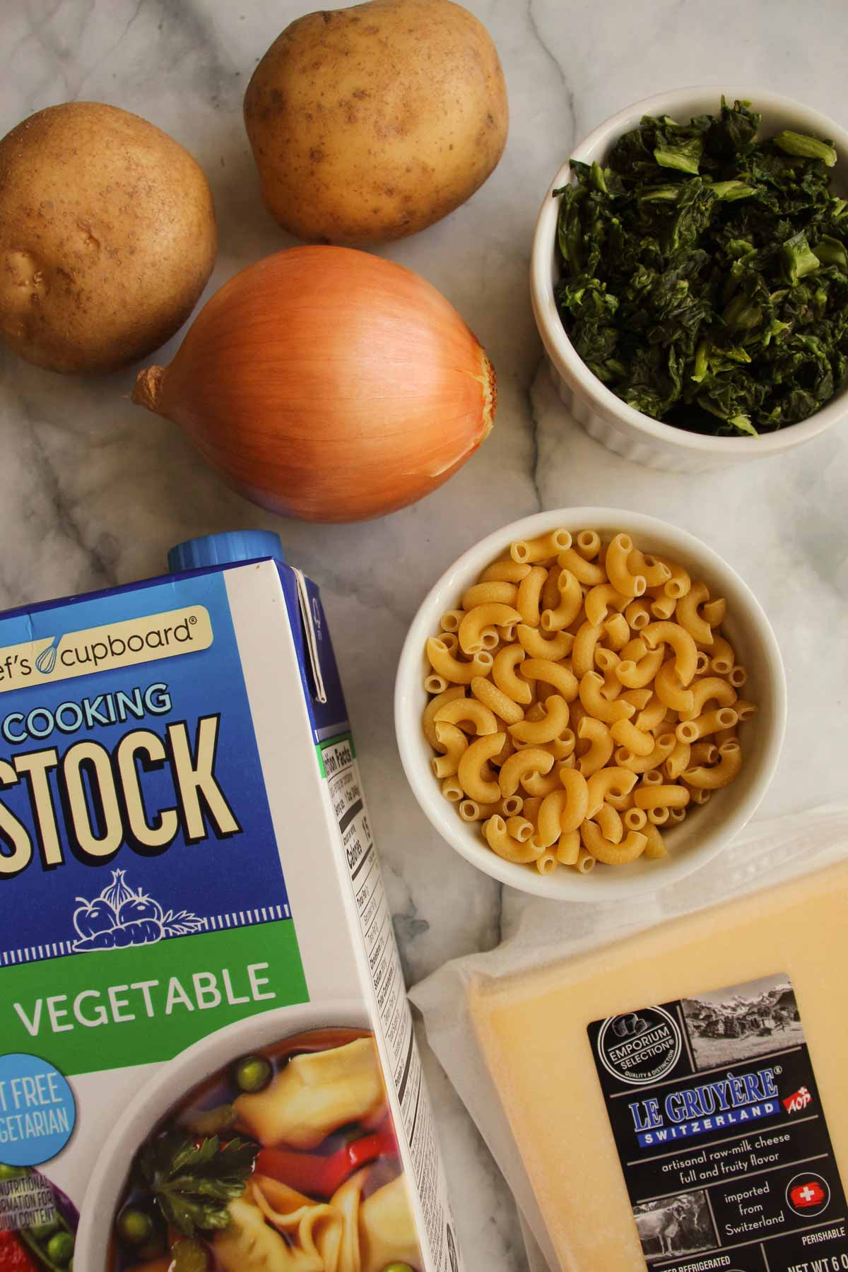 Potatoes, onion, cooked spinach, elbow macaroni, a carton of vegetable stock, and Gruyere cheese.