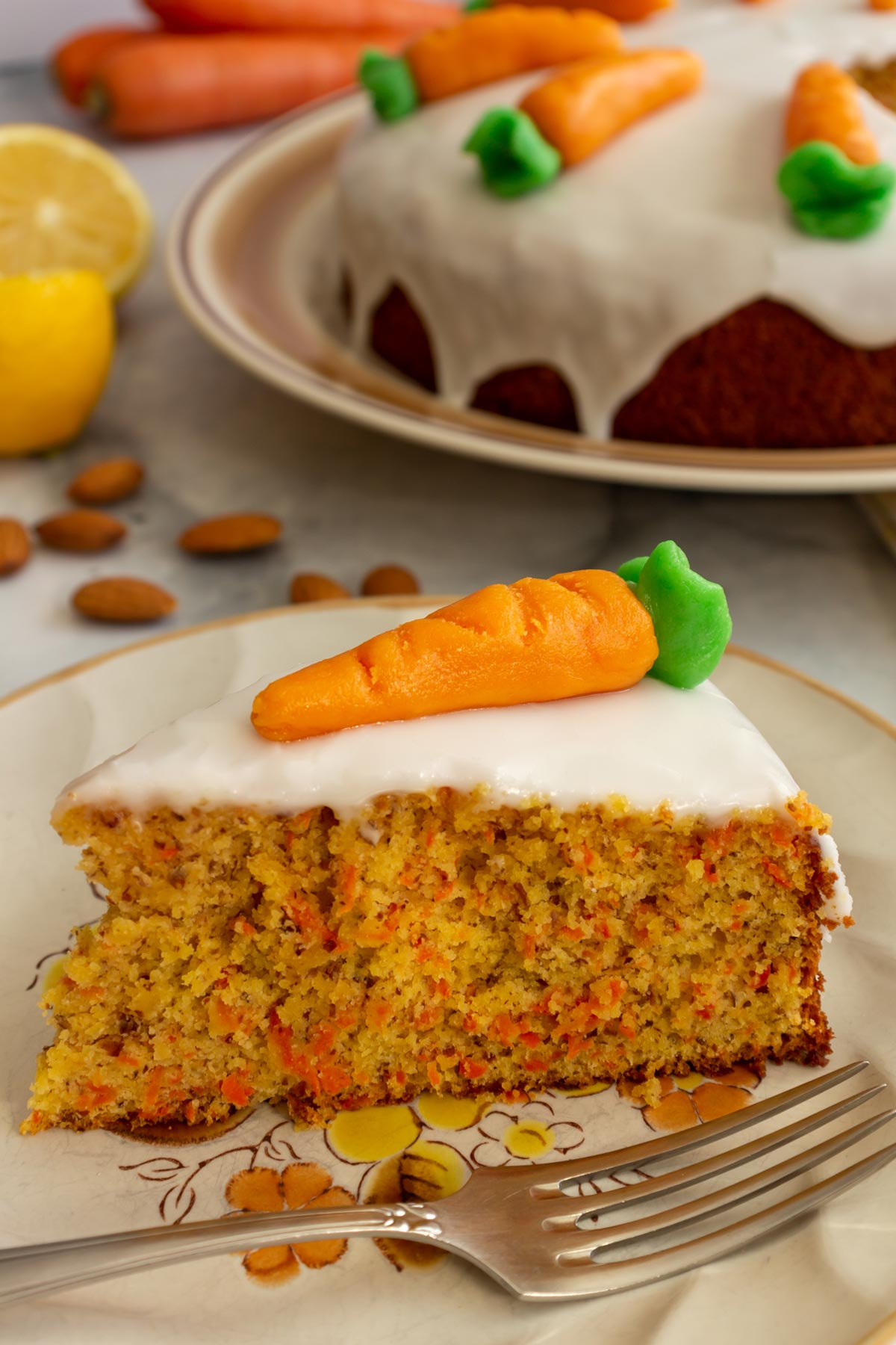 Closeup of a slice of Swiss carrot cake topped with a marzipan carrot on a plate.
