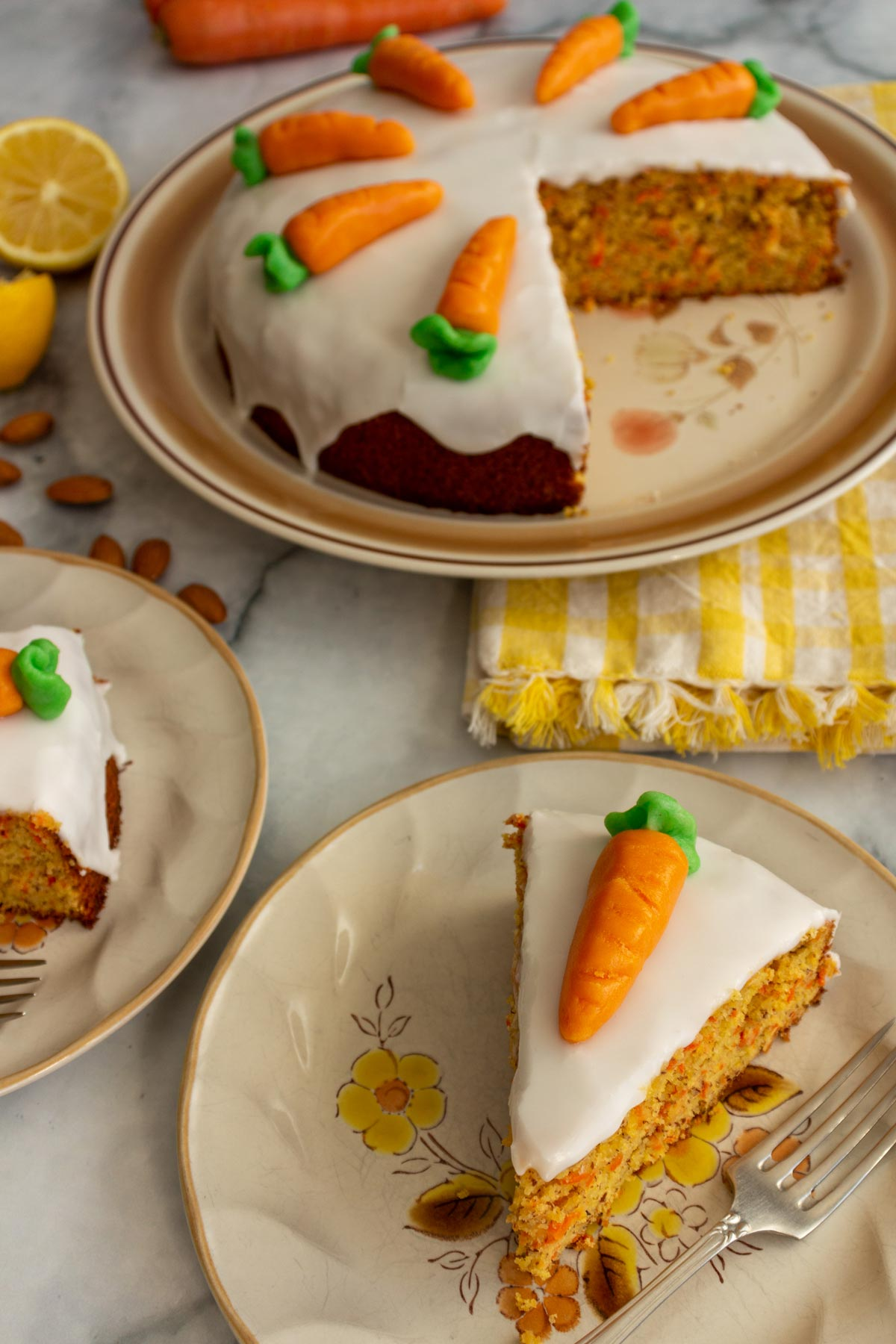 Sliced Swiss carrot cake on plates with remaining cake, lemons, and carrots in the background.