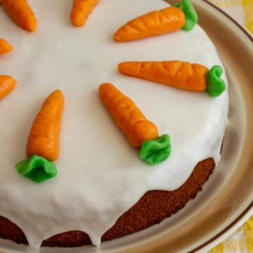 A glazed Swiss carrot cake topped with marzipan carrots on a rustic round serving dish.