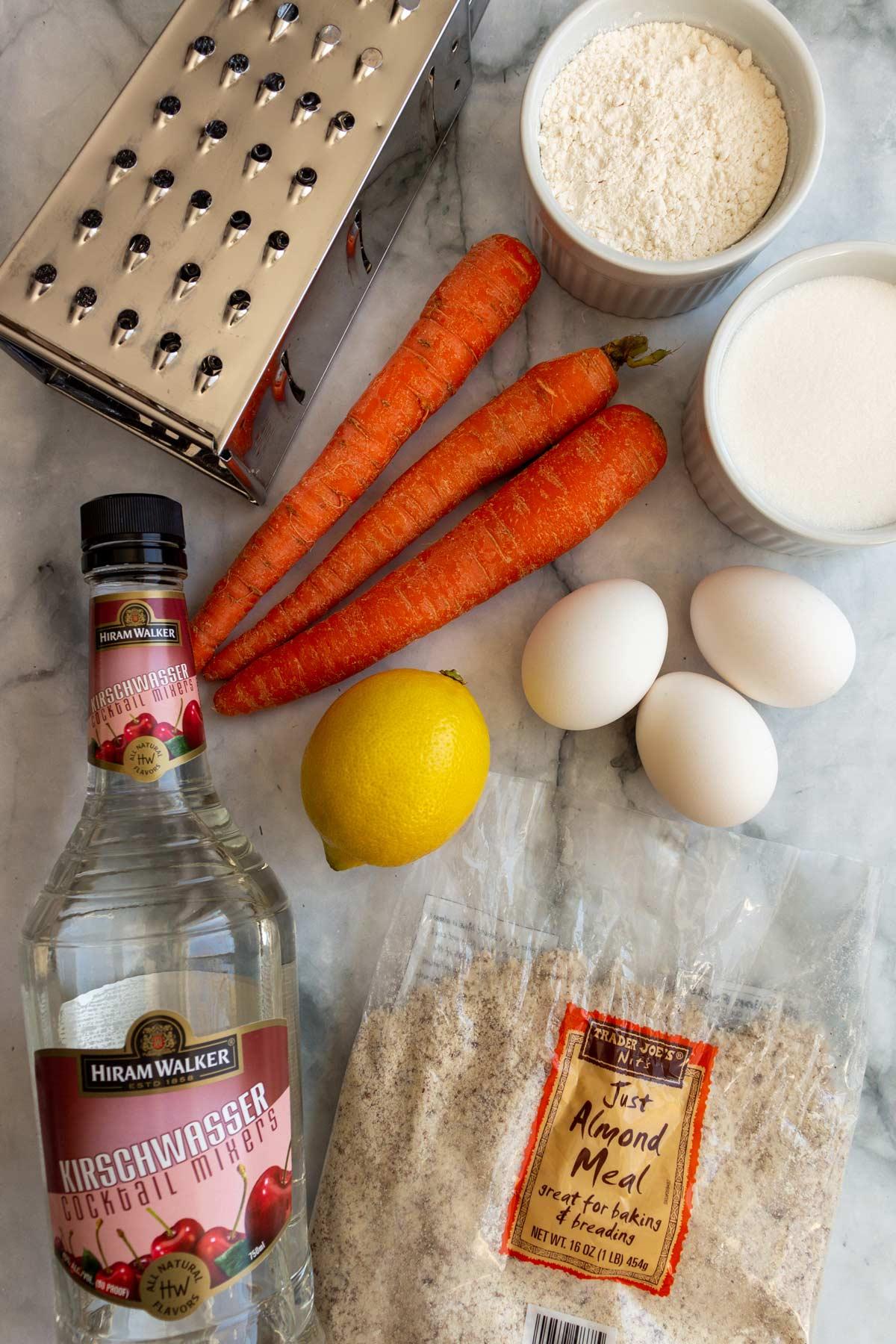 A box grater, carrots, eggs, lemon, almond meal, Kirsch, flour, and sugar.