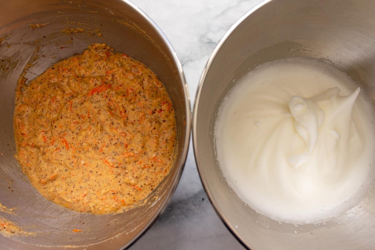 A metal bowl of carrot cake mixture next to a metal bowl of beaten egg whites.