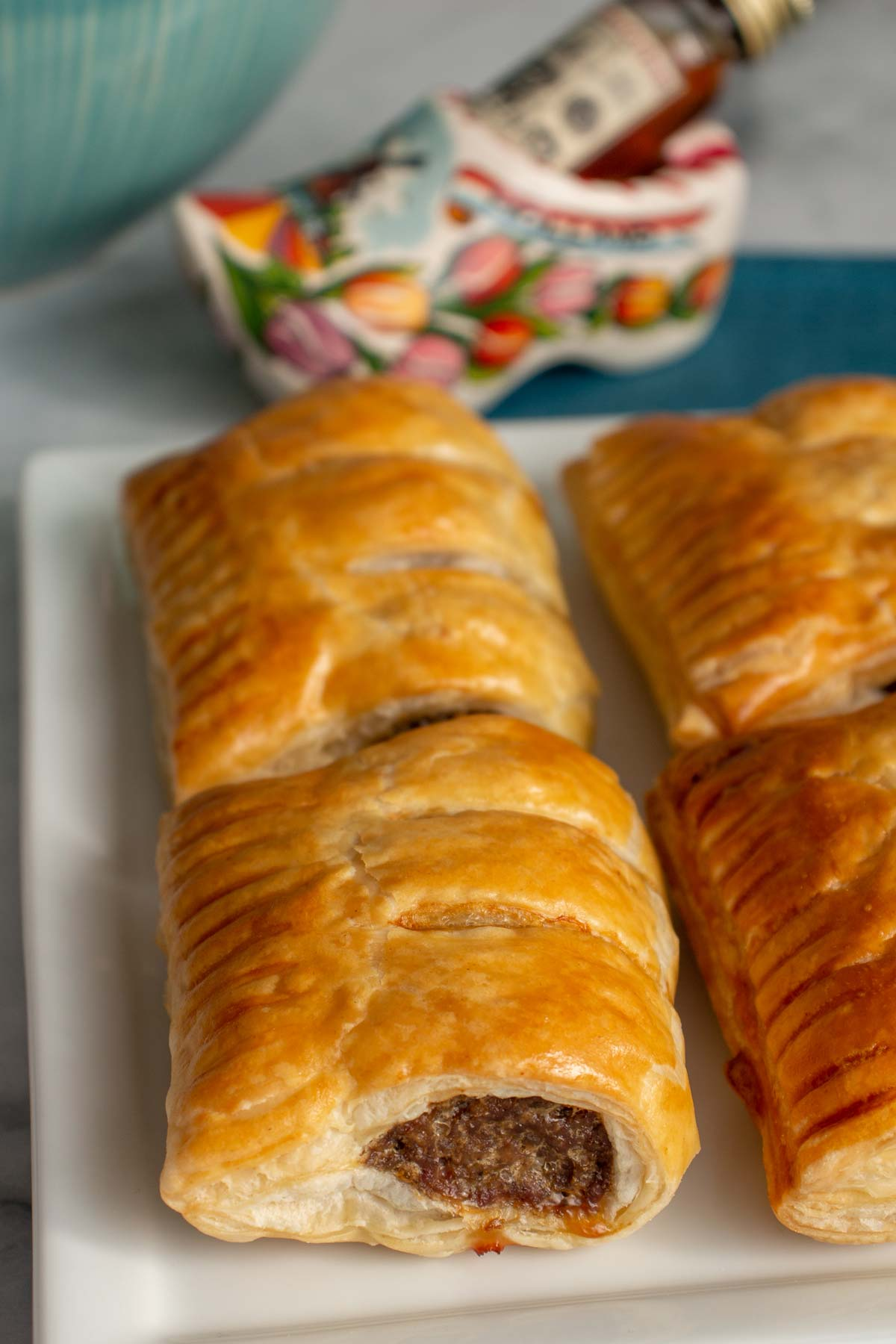 Closeup of Dutch sausage rolls on a plate with a wooden shoe figurine in the background.