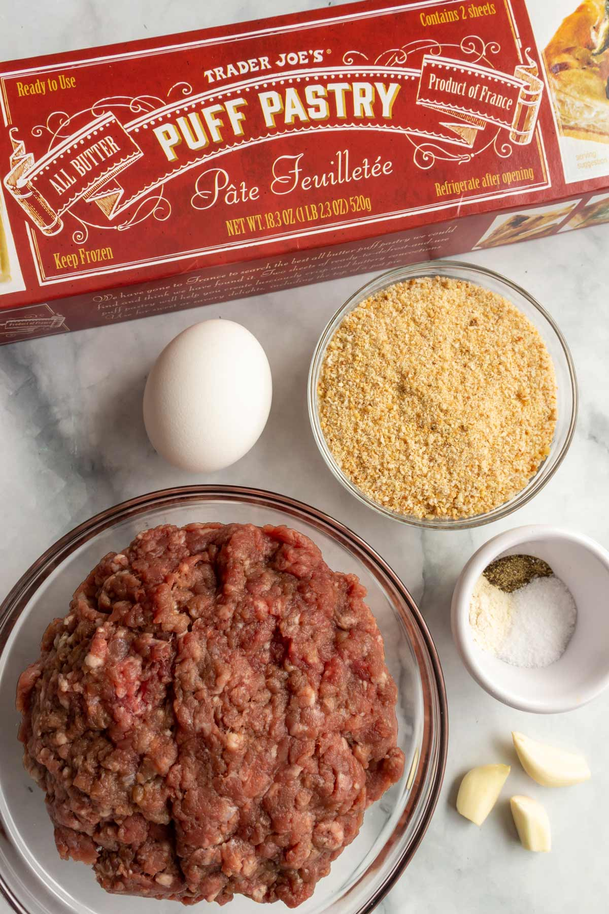 A box of puff pastry, an egg, bowls of breadcrumbs, spices, and ground beef.