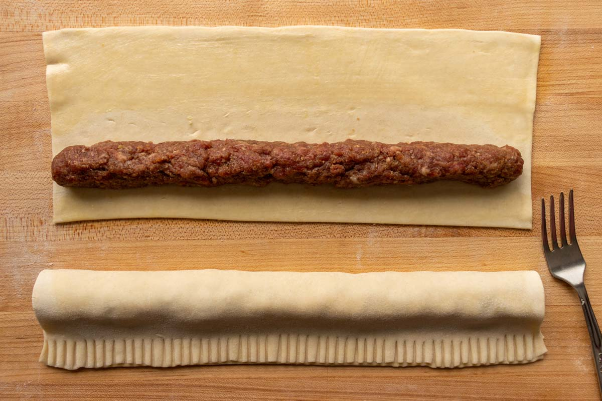 Two strips of puff pastry, one topped with ground meat, the other folded over.