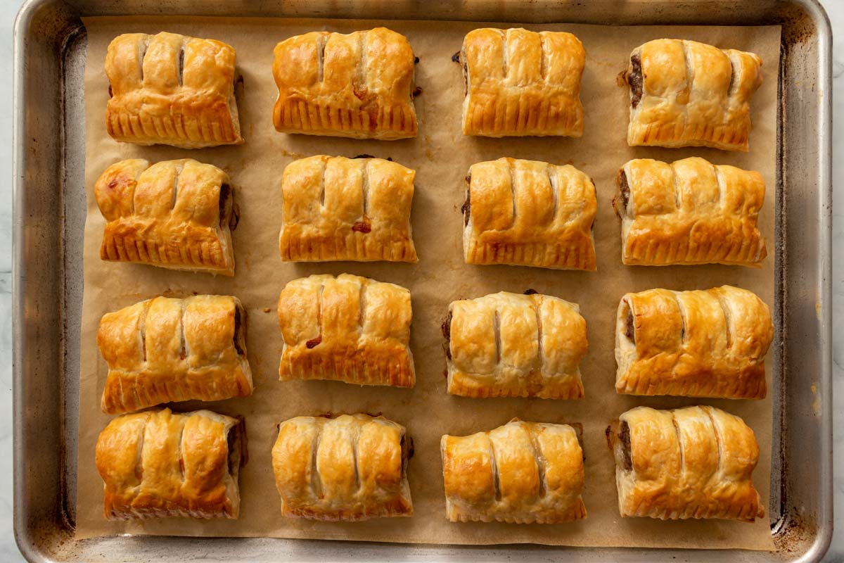 Baked Dutch sausage rolls arranged on a parchment paper lined baking sheet.