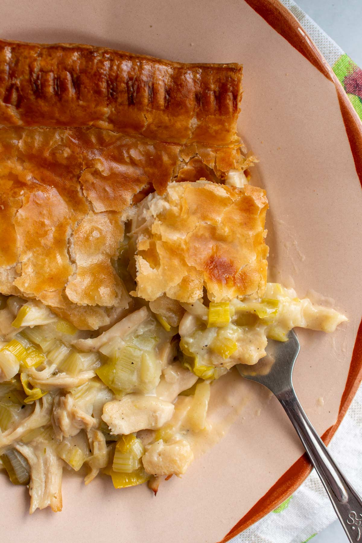 Closeup of chicken and leek pie on a rustic plate with a fork scooping some up.