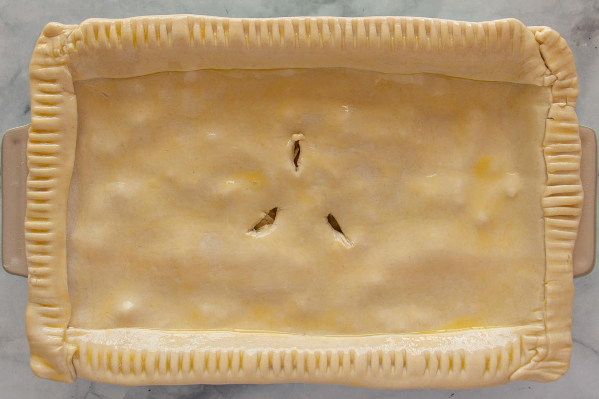 A rectangular baking dish topped with unbaked puff pastry with 3 slits cut in the center.