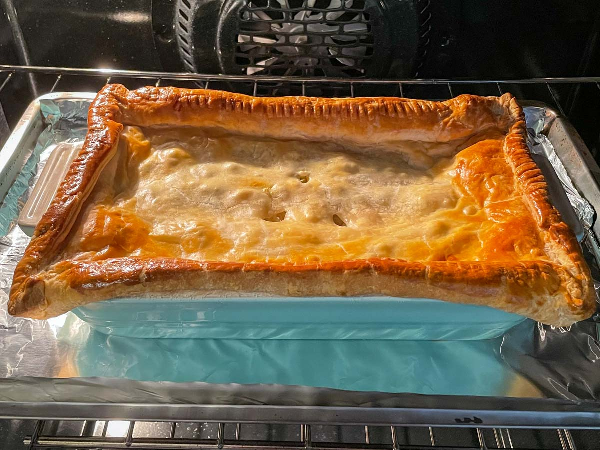A rectangular blue baking dish of savory pie baking in the oven.