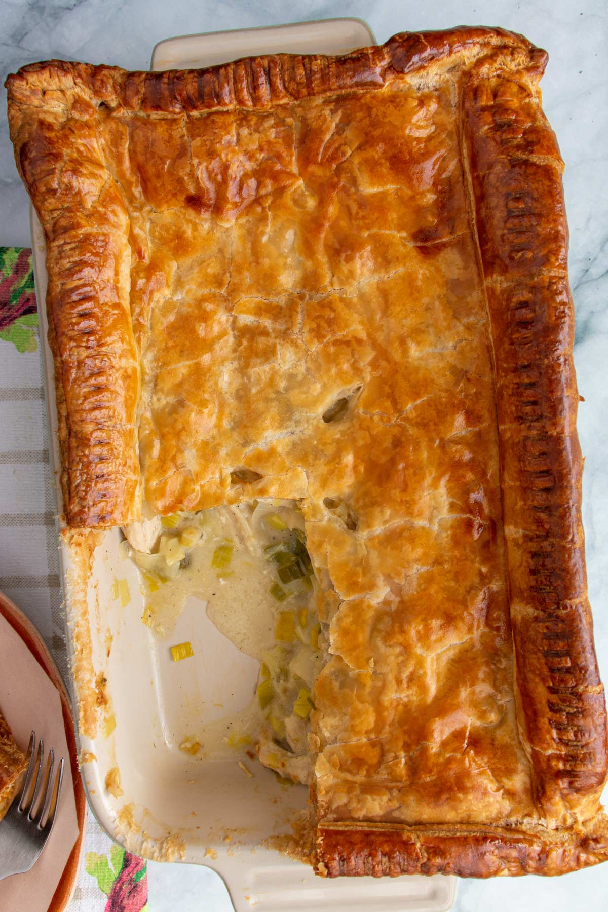A rectangular savory pie in a ceramic baking dish with a square portion cut out.