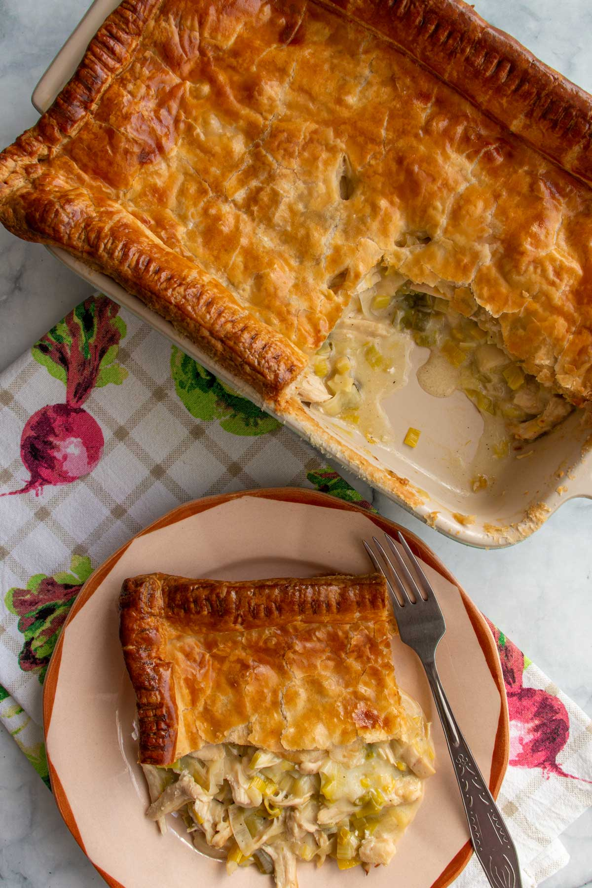A rectangular baking dish of chicken and leek pie with one serving on a plate.