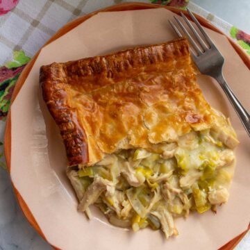 Closeup of a portion of chicken and leek pie with a fork on a rustic plate.