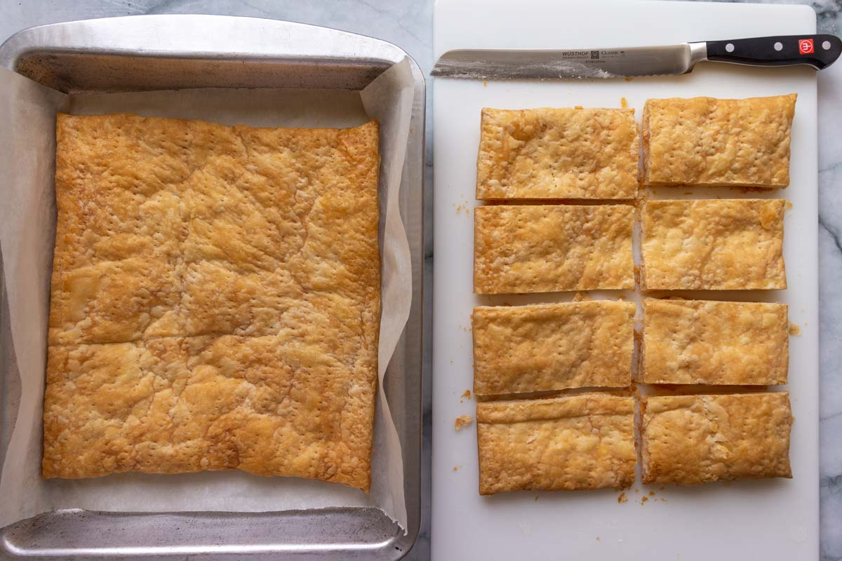 A sheet of baked puff pastry in a pan next to a sheet cut into rectangles.