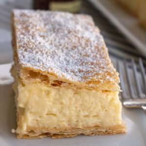 A cream slice topped with powdered sugar on a white plate with a fork beside it.