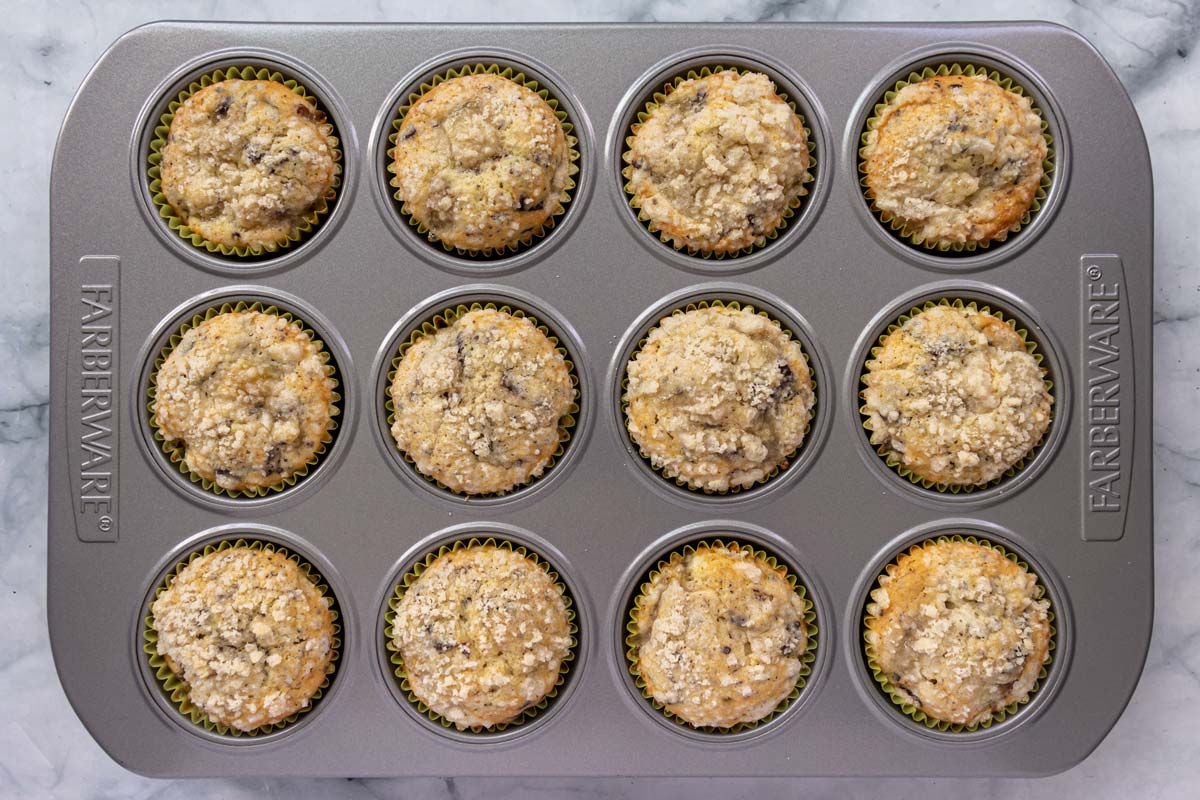 A pan of baked muffins in yellow paper liners topped with crumbly streusel topping.