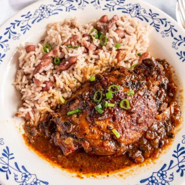 Jamaican brown stew chicken and rice and peas in a white shallow bowl with blue trim.