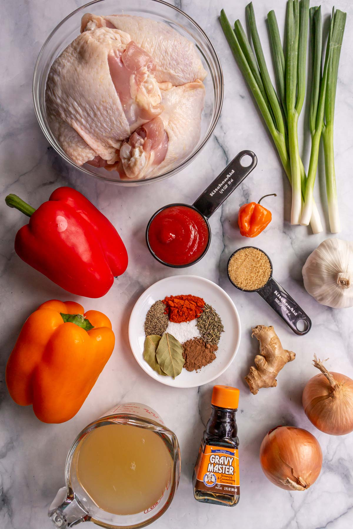 Ingredients for Jamaican brown stew chicken on a white marble background.