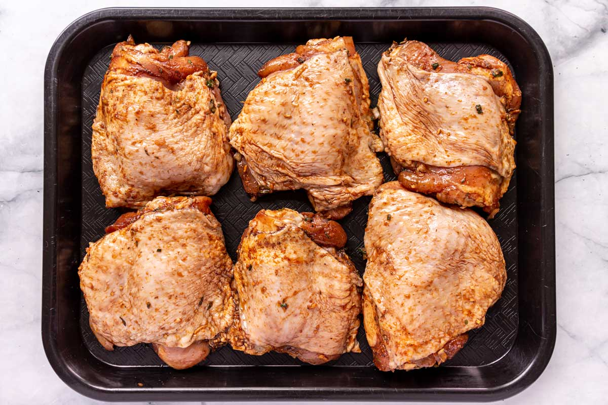 Six skin-on bone-in marinated chicken thighs arranged on a black cafeteria tray.