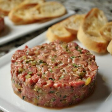 Closeup of steak tartare shaped into a round disc on a white plate with toasted baguette slices.