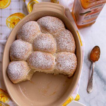 An oval baking dish half filled with powdered sugar dusted buchteln, Austrian stuffed sweet rolls.