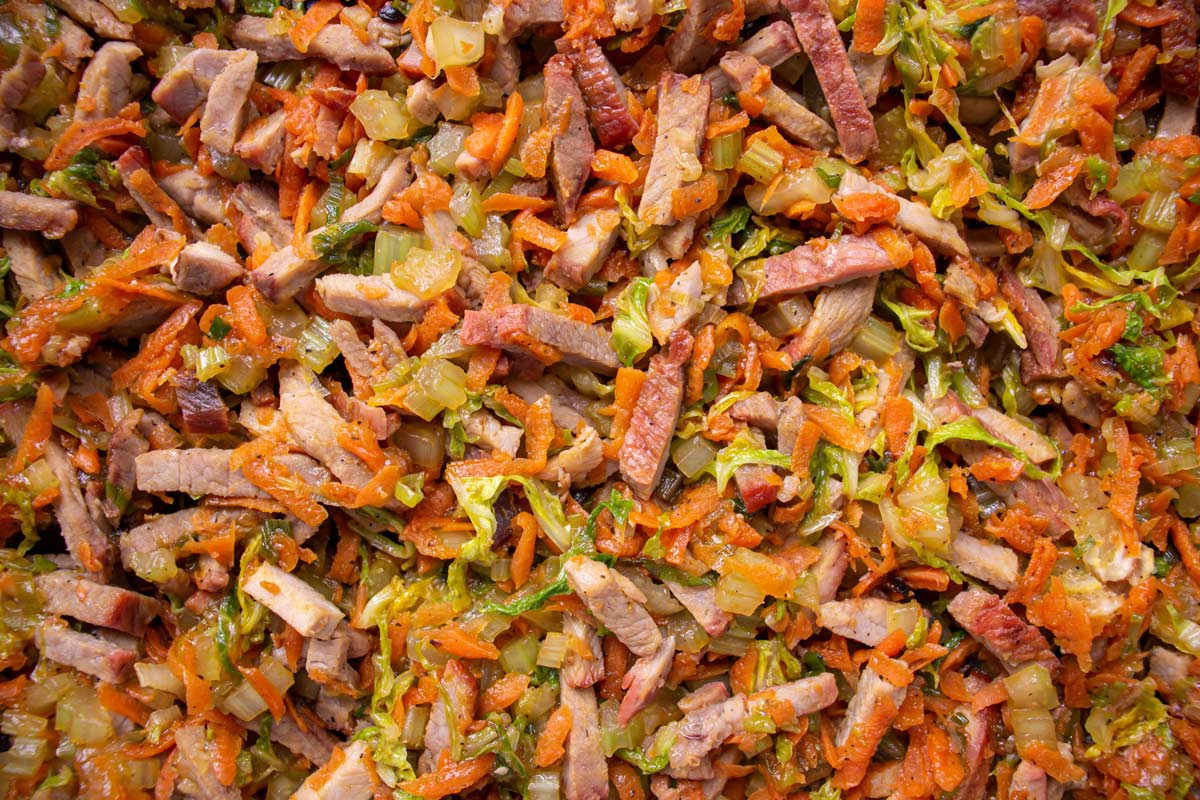 Closeup of char siu pork and vegetable egg roll filling with cabbage and carrots.