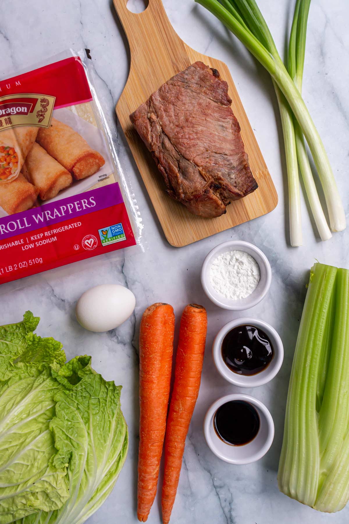 Ingredients for pork and vegetable egg rolls on a white marble background.
