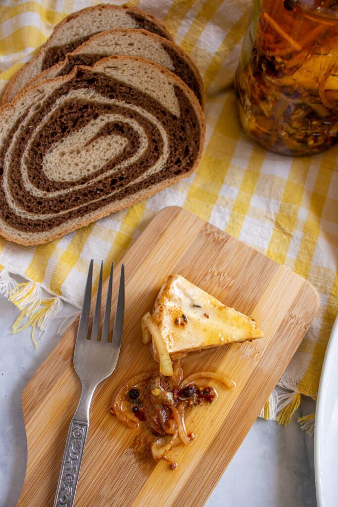 A wedge of Czech marinated cheese on a board next to sliced marble rye bread.