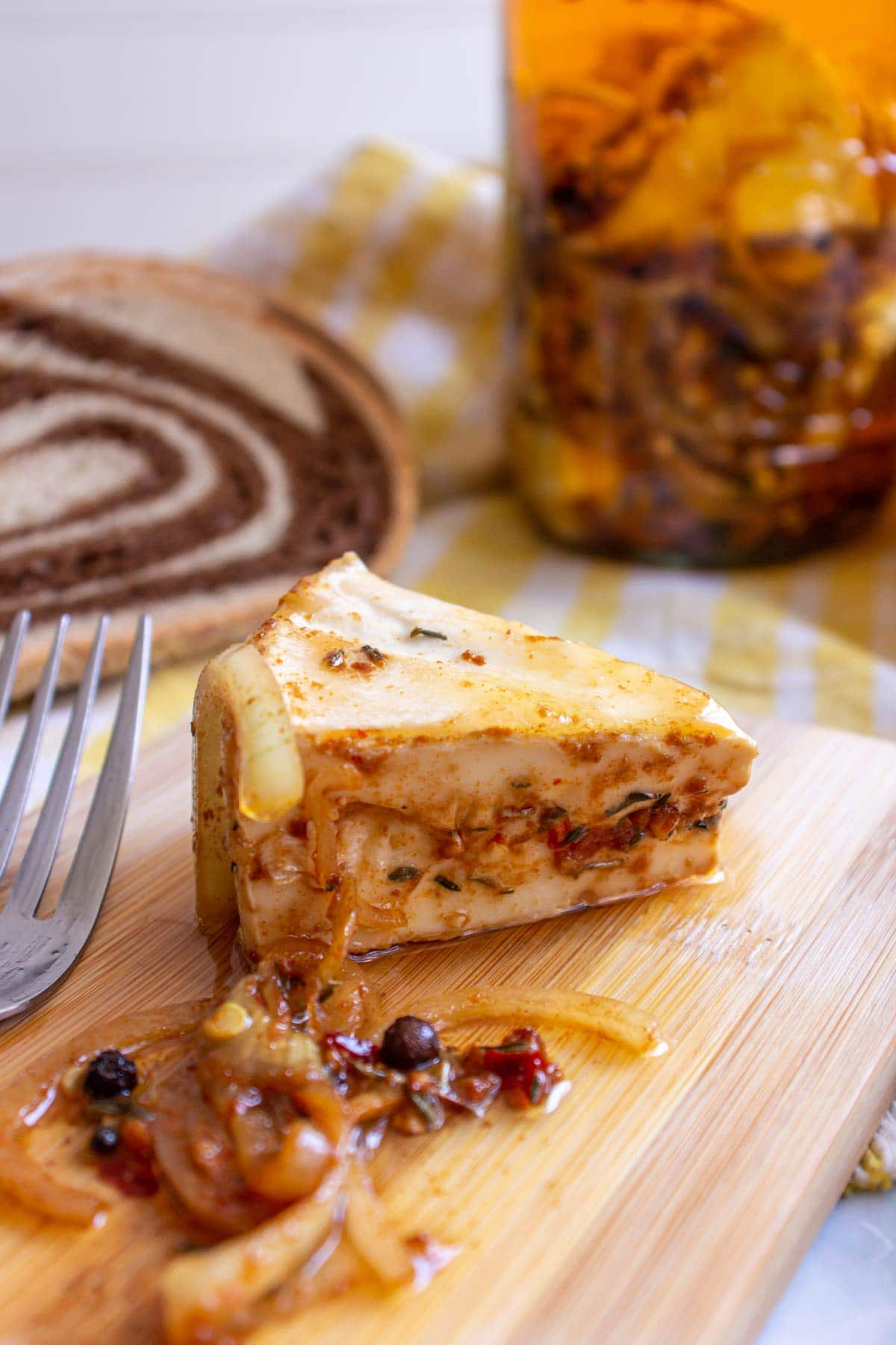 A wedge of Czech marinated cheese with onions and spices on a small wooden board.
