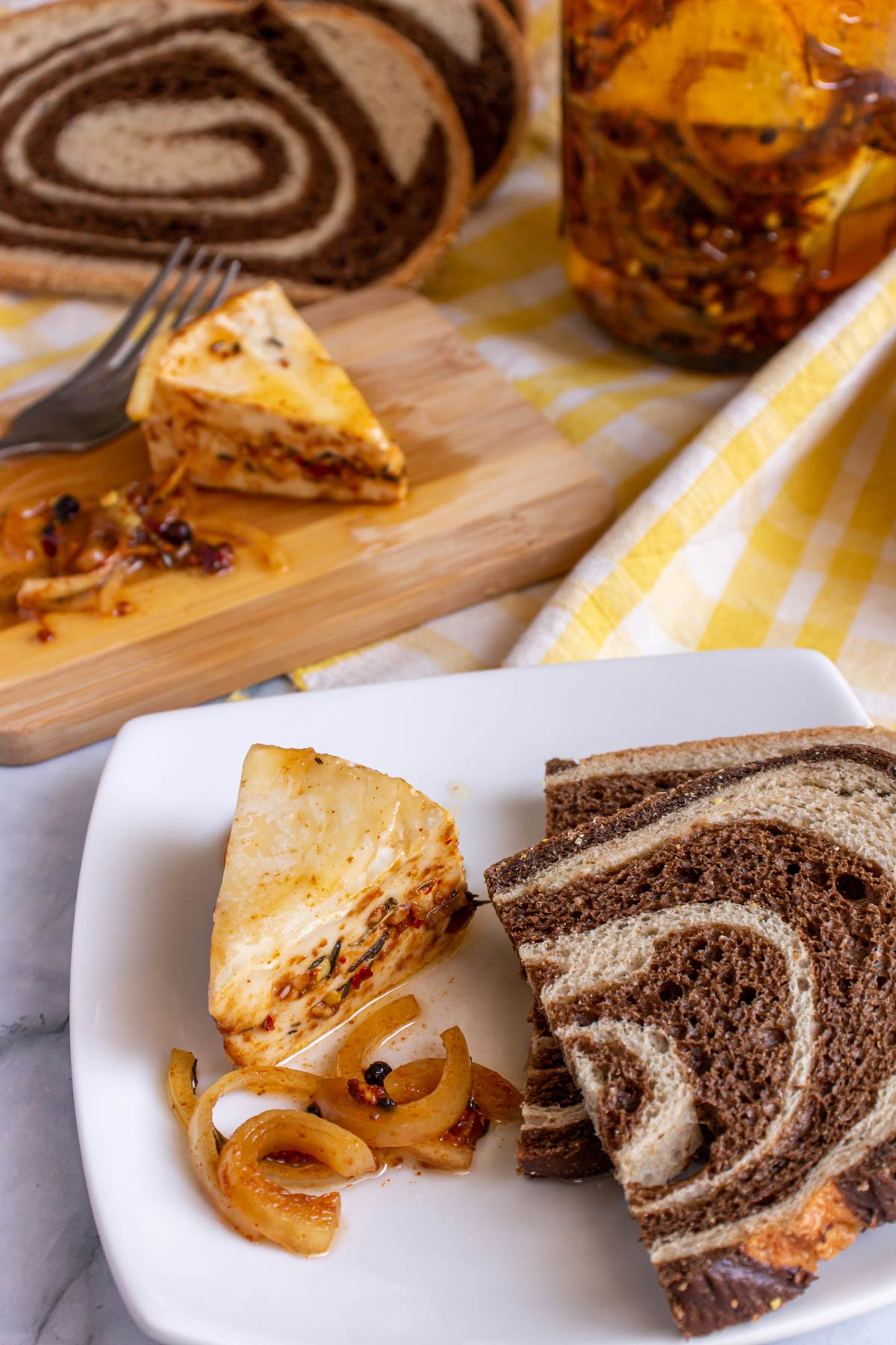 Wedges of marinated cheese on a plate and wooden board with sliced marble rye bread.