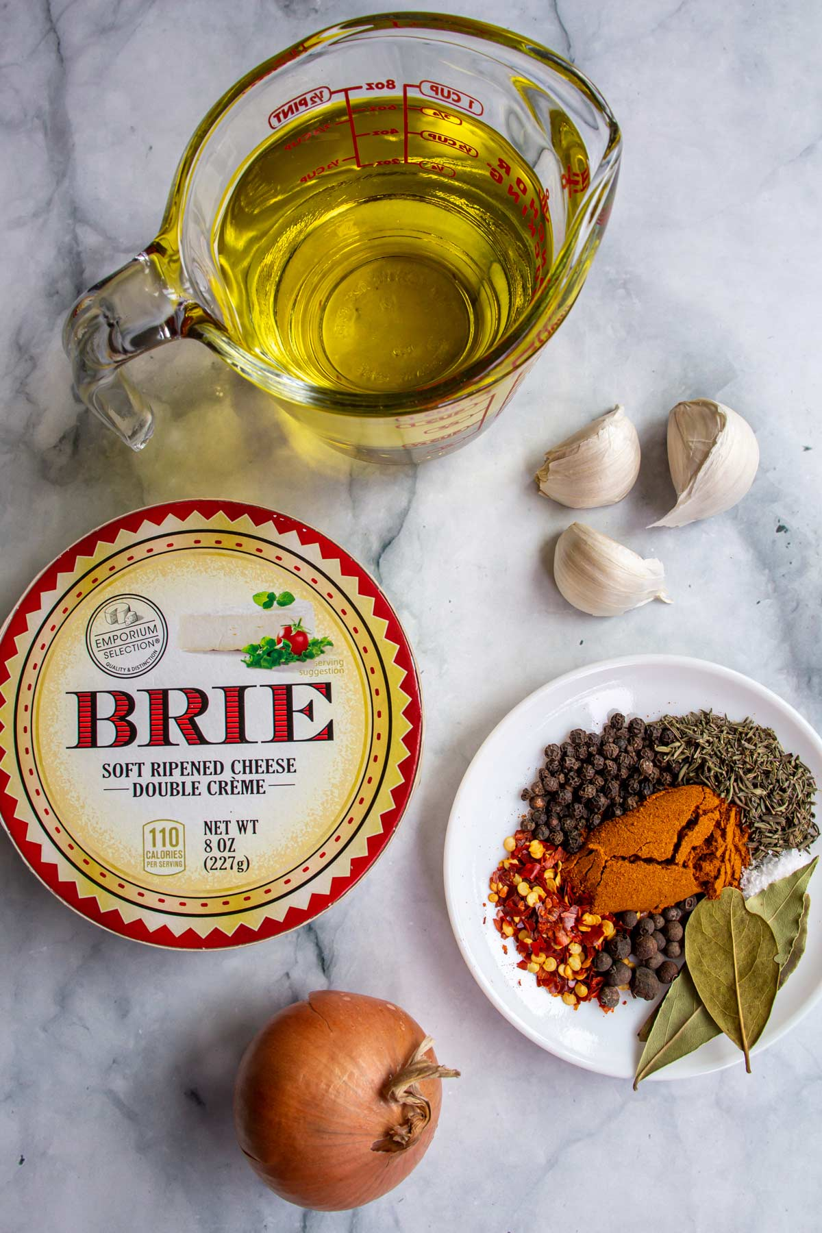 Ingredients for Czech marinated cheese on a white marble background.