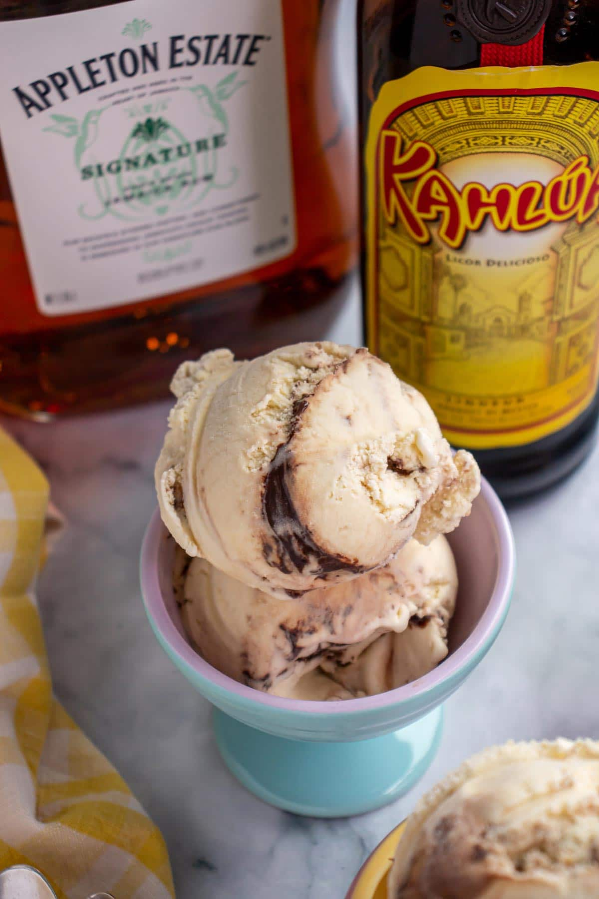 Two scoops of ice cream in a blue ceramic dish with alcohol bottles in the background.
