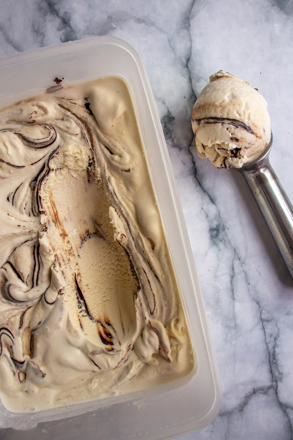A rectangular container of ice cream with an ice cream scoop of ice cream beside it.